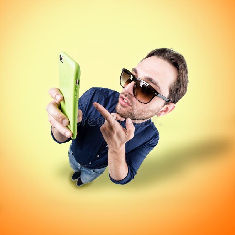 De Latijnse minnaar maakt een grappig gezicht met zijn telefoon royalty-vrije stock afbeeldingen