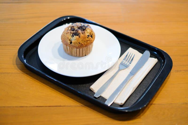 De lava van de muffinchocolade met chocoladeschilfer en banaangeur in document kop dient met reeks van plaat, vork en mes voor de stock foto