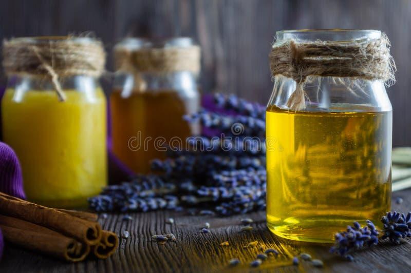 De lavendel en kruidenhoning in glaskruiken en de lavendel bloeien op donkere houten achtergrond royalty-vrije stock foto