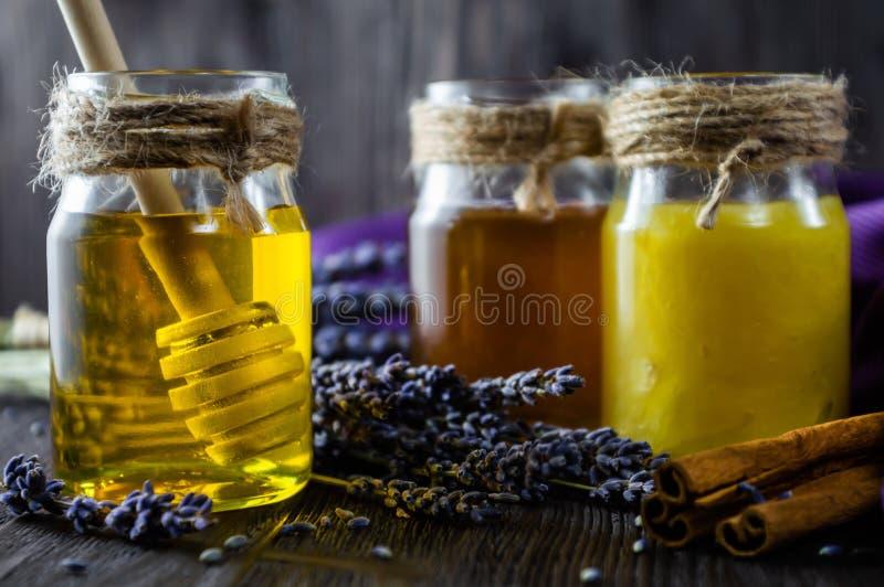 De lavendel en de kruidenhoning in glaskruiken met honing lepelen op donkere houten achtergrond stock foto