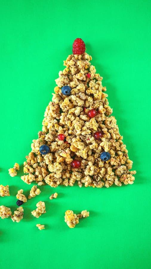 De lay-outgranola of muesli van de Kerstmis gezonde levensstijl in vorm van Kerstboom met ballen van bessen en frambozen op boven stock foto