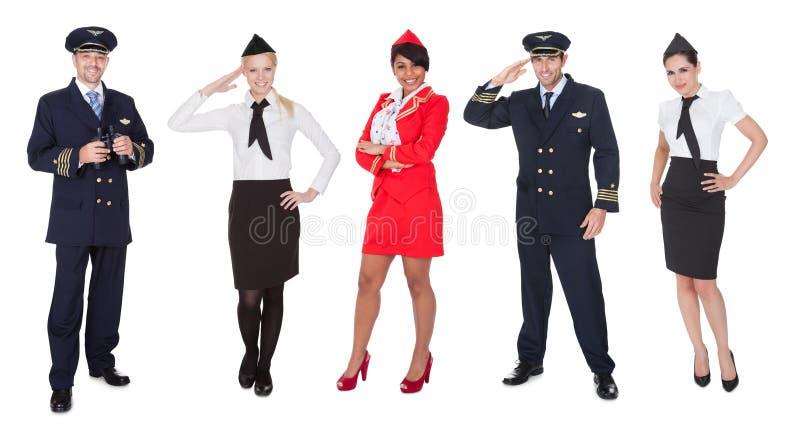 De leden van de vliegtuigbemanning, loodsen, stewardessen stock fotografie