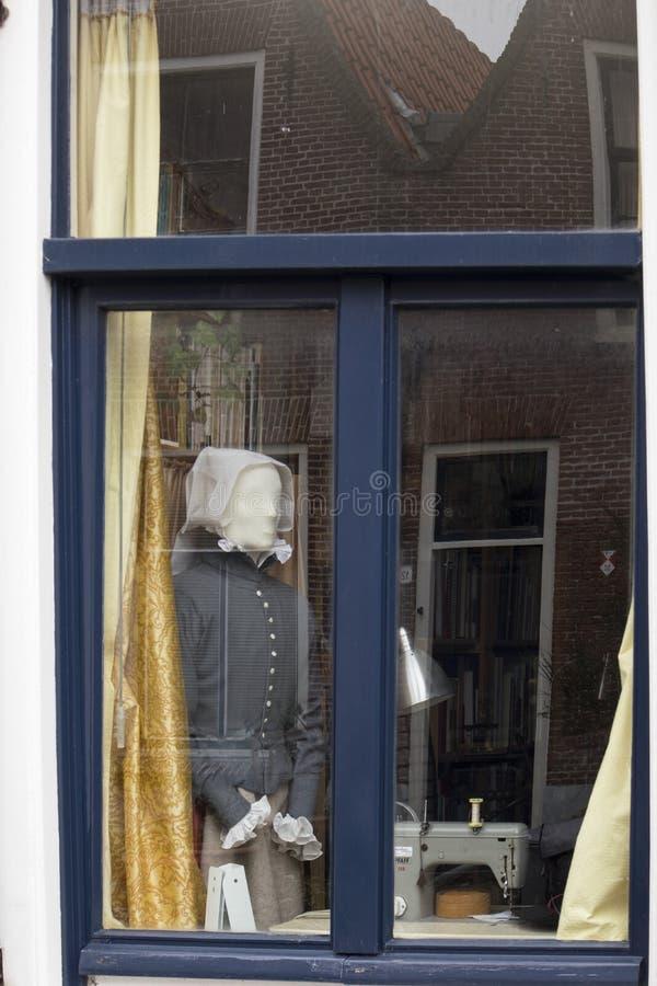 De ledenpop kleedde zich omhoog in een traditioneel Nederlandse in een GLB en schort in het venster van het huis royalty-vrije stock foto