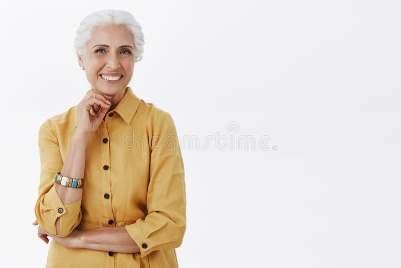 De leeftijd is onzin Portret van gelukkige charismatische modieuze hogere vrouw met wit haar in het in gele laag stellen met stock afbeelding