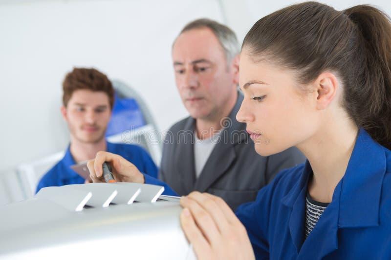 De leerling van de airconditioningsreparatie bevestigt industriële compressoreenheid stock foto's