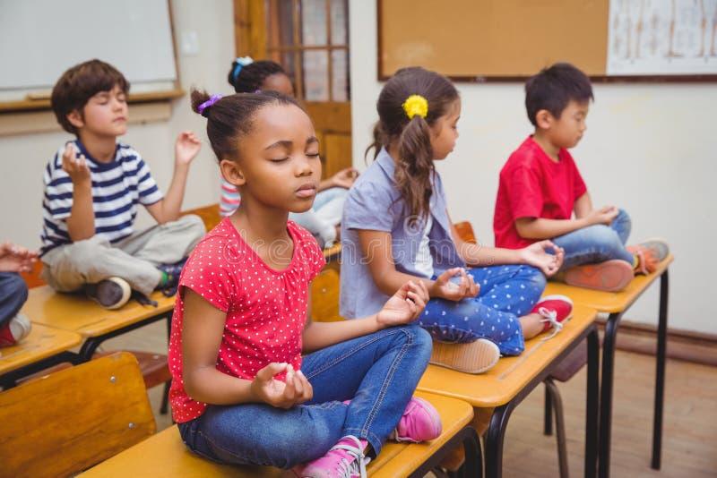 De leerlingen die in lotusbloem mediteren plaatsen op bureau in klaslokaal royalty-vrije stock afbeelding