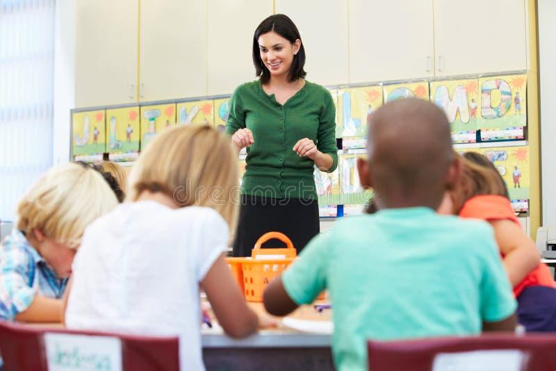 De Leerlingen van leraarstalking to elementary in Klaslokaal stock afbeelding