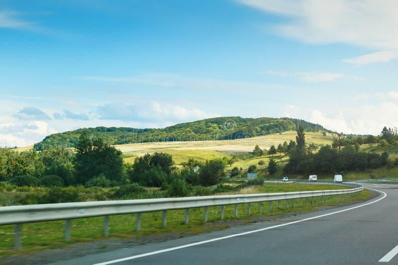 De lege asfaltweg en de blauwe hemel met witte wolken op de zonnige dag Klassieke panoramamening van weg door gebieden royalty-vrije stock afbeelding