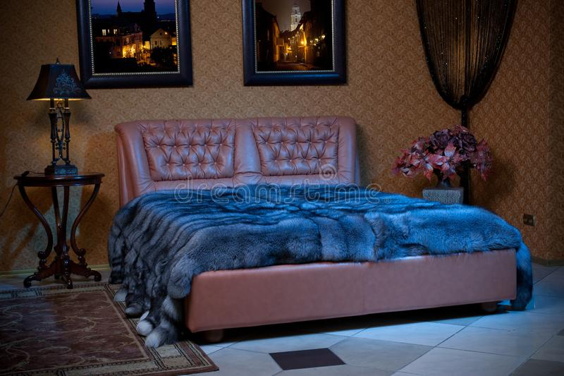 De lege binnenlandse slaapkamerachtergrond in warme kleuren verfraaide met klassiek meubilair, lampen, bank en bont stock foto's