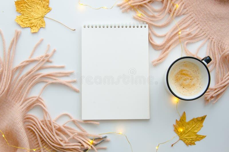 De lege blocnote op de witte lijst met gebreide roze sjaal, koffiemok en de herfst gaat weg Hoogste mening Ruimte voor tekst royalty-vrije stock foto