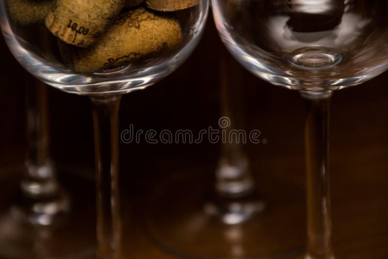 De lege die wijnglazen en een glas met wijn wordt gevuld kurken op een donkere bosrijke achtergrond stock foto