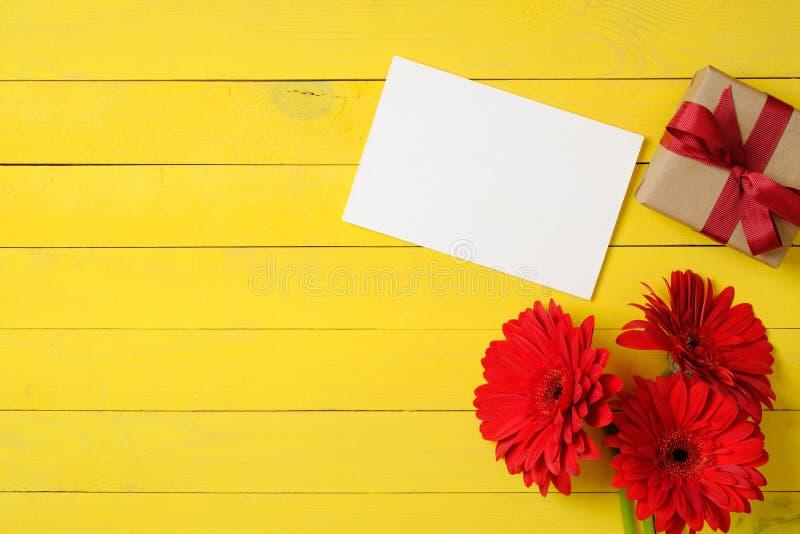 De lege document kaart, de rode madeliefjebloemen en het giftvakje met lint buigen op heldere gele achtergrond Gelukwens of vieri stock foto