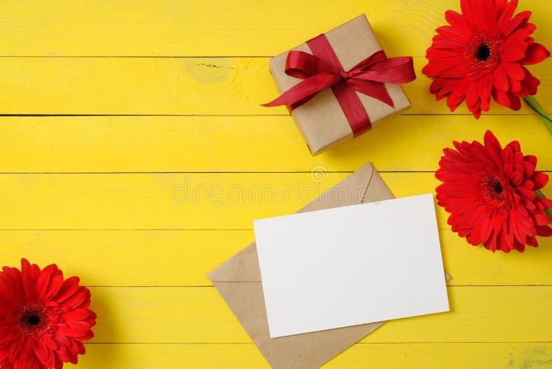 De lege document kaart, uitstekende envelop, rood madeliefje bloeit, giftvakje op gele houten achtergrond Vrouwenbureau Gelukwens royalty-vrije stock afbeeldingen