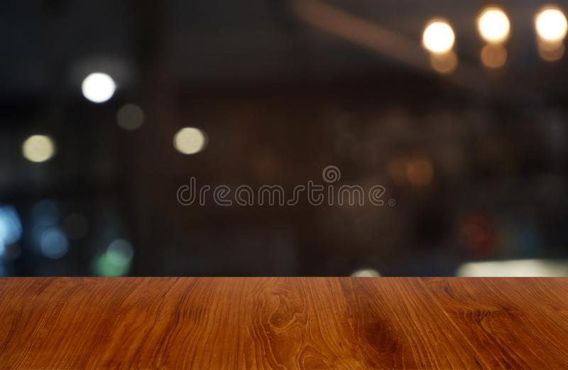De lege donkere houten lijst voor samenvatting vertroebelde achtergrond van koffie en koffiewinkelbinnenland Kan voor vertoning w royalty-vrije stock fotografie