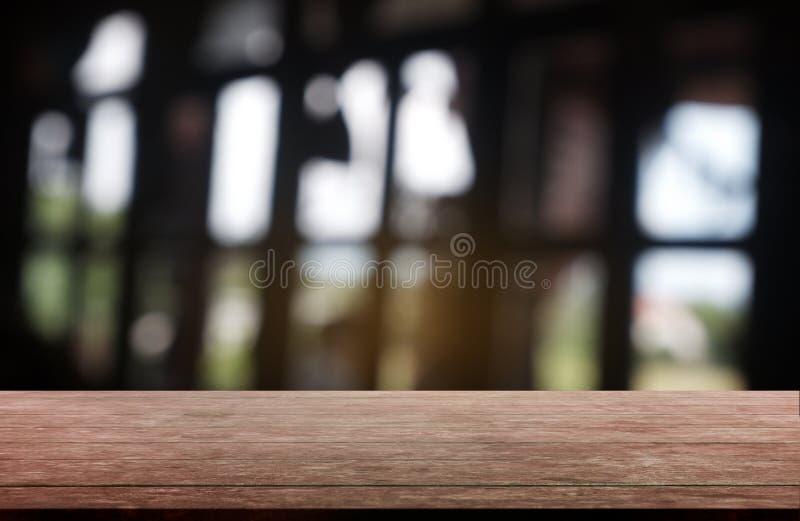 De lege donkere houten lijst voor samenvatting vertroebelde achtergrond van restaurant, koffie en koffiewinkelbinnenland kan word stock afbeeldingen