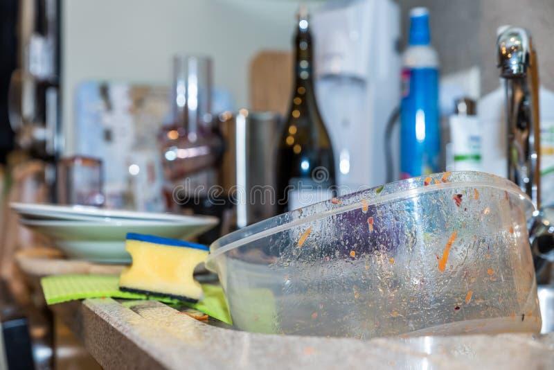 De lege gebruikte vuile plastic doos van de voedselcontainer in de gootsteen van de keukenwas stock fotografie