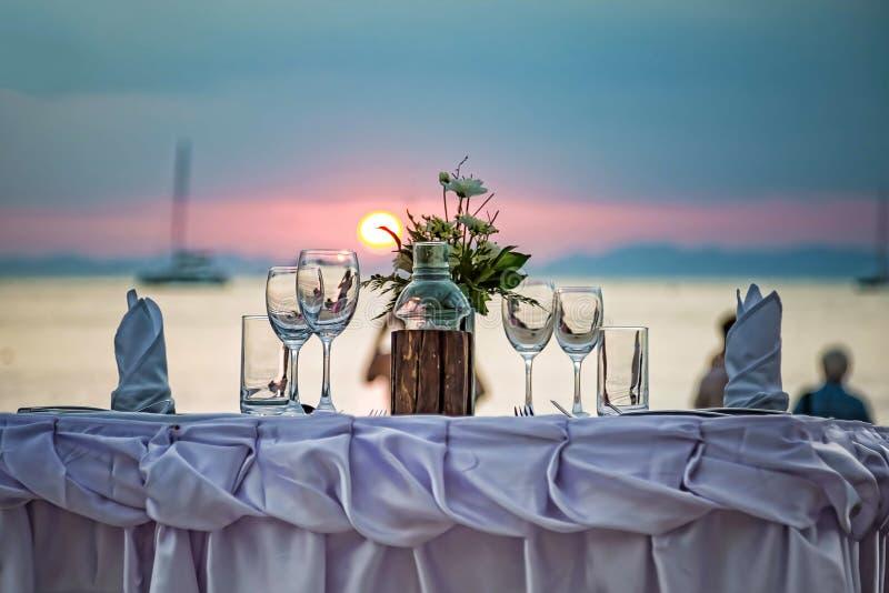 De lege glazen zijn op de gediende lijst Tegen de achtergrond van een zonsondergang in het overzees op een zandig strand stock afbeeldingen