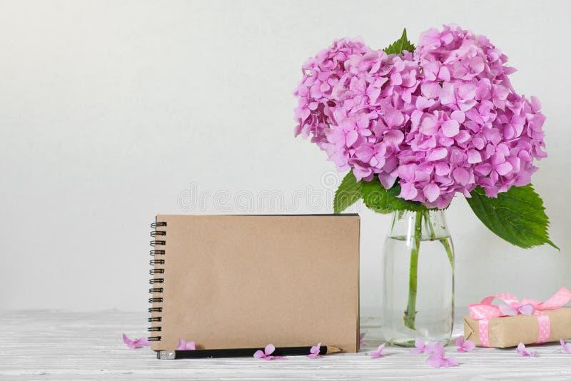 De lege groetkaart met roze hydrangea hortensia bloeien en de giftdoos op witte achtergrond Modern stilleven royalty-vrije stock afbeelding