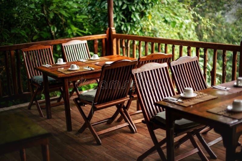 De lege houten stoelen en de lijsten, met koffie vormen binnen bovenkant - neer - klaar voor ochtendontbijt tot een kom, wilderni royalty-vrije stock fotografie