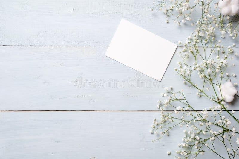 De lege kaart voor uitnodiging of gelukwens, weinig giftvakje, bos van gypsophila bloeit op lichtblauwe houten lijst Bannermocku stock afbeelding