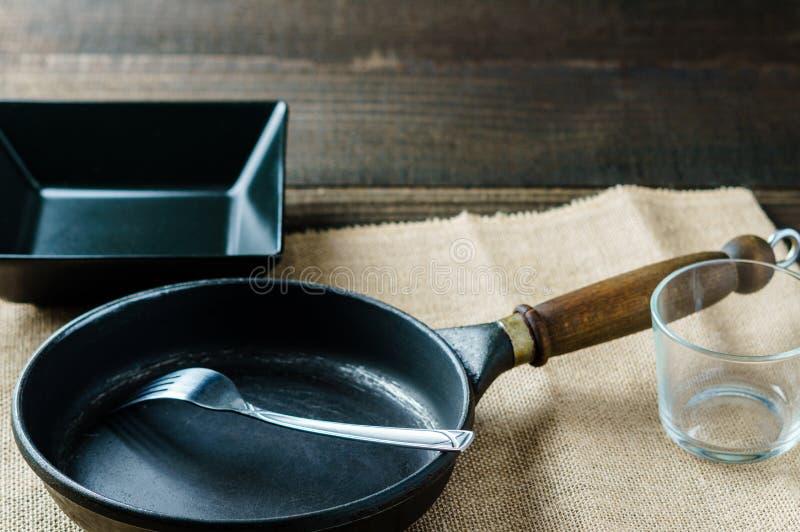 De lege kop van het keukenwerktuig, plaat, vork, pan, op de opstelling van het lijststilleven stock afbeelding