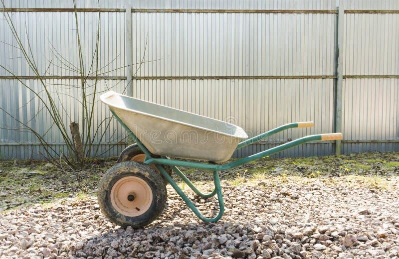 De lege kruiwagen op het tuinperceel is op het puin royalty-vrije stock afbeeldingen