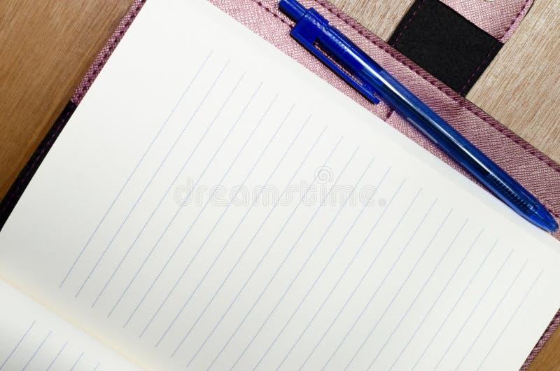 De lege lederen cover-laptop opent op een houten vloer met een blauwe pen die wordt gebruikt om zelfs de herinneringen van de wer stock foto's