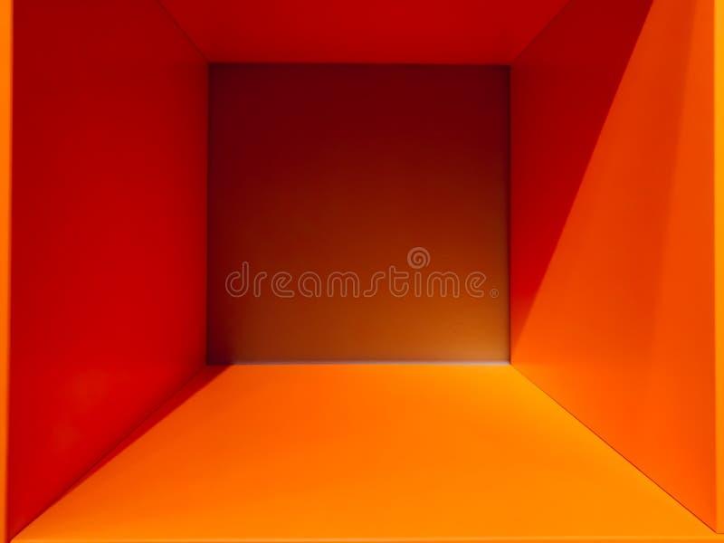 De lege oranje ruimte van de gradiëntruimte, binnenlands voor ontwerp en decoratie - abstracte achtergrond vierkante doos met leg stock foto