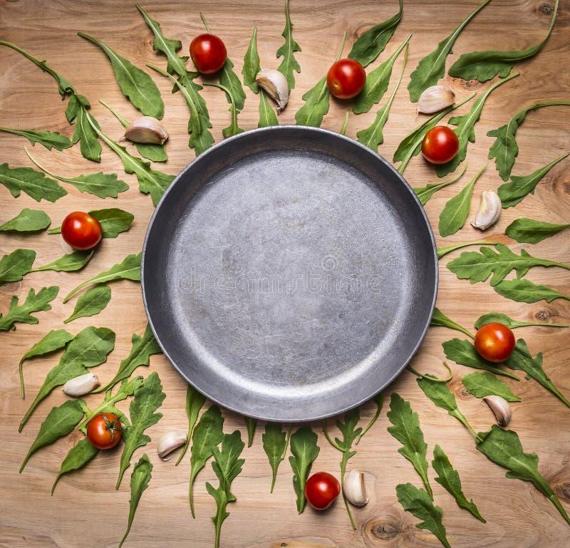 De lege pan met tomaten en kruiden rond plaats voor tekst, kader op houten rustieke bovenkant als achtergrond wedijvert royalty-vrije stock foto