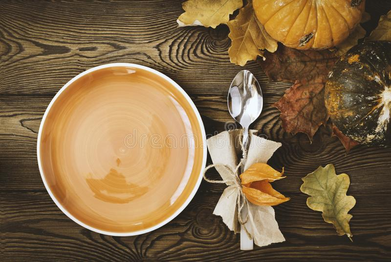 De lege plaat klaar voor plaatsing van voedsel, bestek, kleurde bladeren op een houten lijst en een pompoen Autumn Table royalty-vrije stock foto