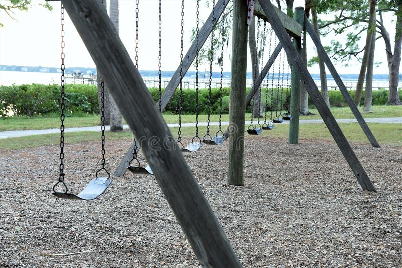De lege verlaten schommeling in een lokaal park wijst op onze vergeten kinderjaren stock afbeeldingen