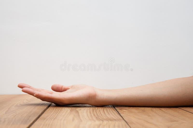 De lege vrouwelijke holding van de vrouwenhand op houten lijst stock foto's