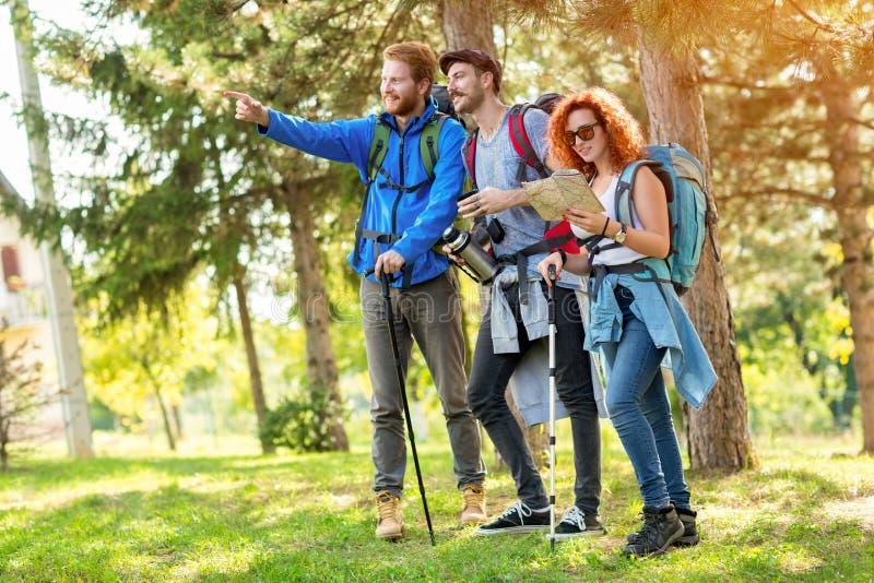 De leider van wandelaarsgroep toont met vingermanier in bos royalty-vrije stock afbeeldingen