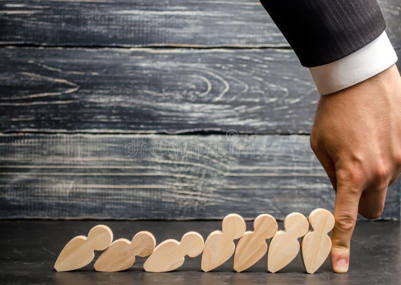 De leiderszakenman houdt dalende domino's tegen Sterke en betrouwbare werkgever Moeilijkheden in zaken en hun oplossing ondersteu stock fotografie