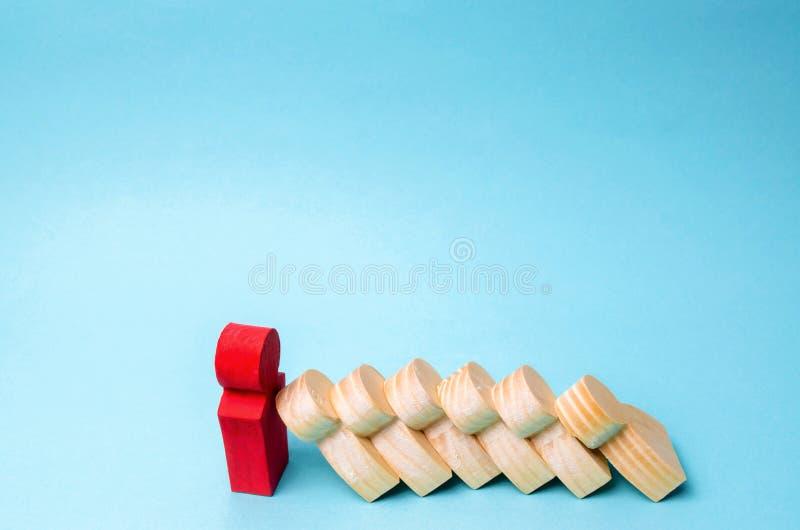De leiderszakenman houdt dalende domino's tegen Sterke en betrouwbare werkgever Moeilijkheden in zaken en hun oplossing ondersteu stock foto's