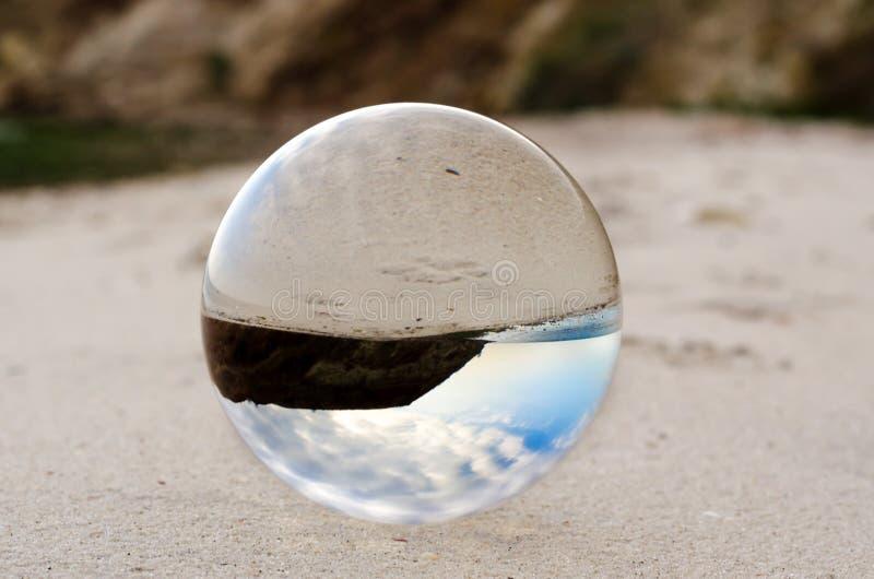 De lens van de glasbal ligt op het zand van de overzeese kust royalty-vrije stock afbeelding
