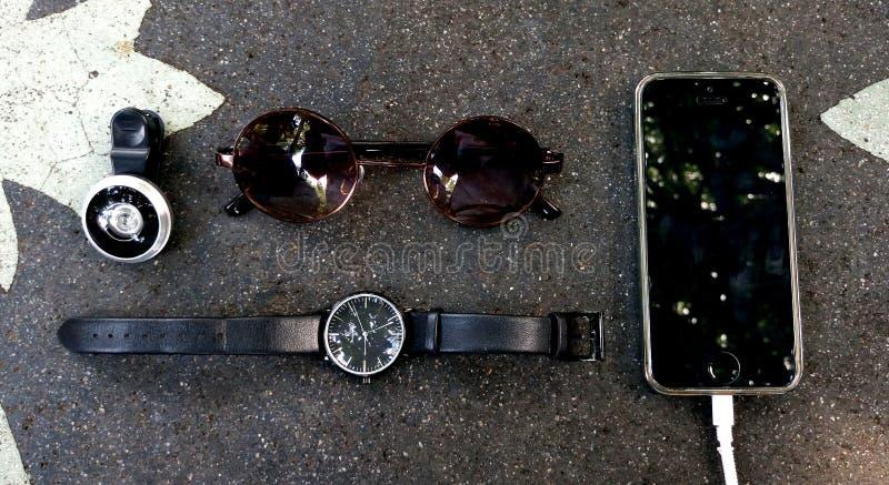De Lens van het vissenoog, Horloge, Sunglass, telefoon op de steenlijst stock foto's