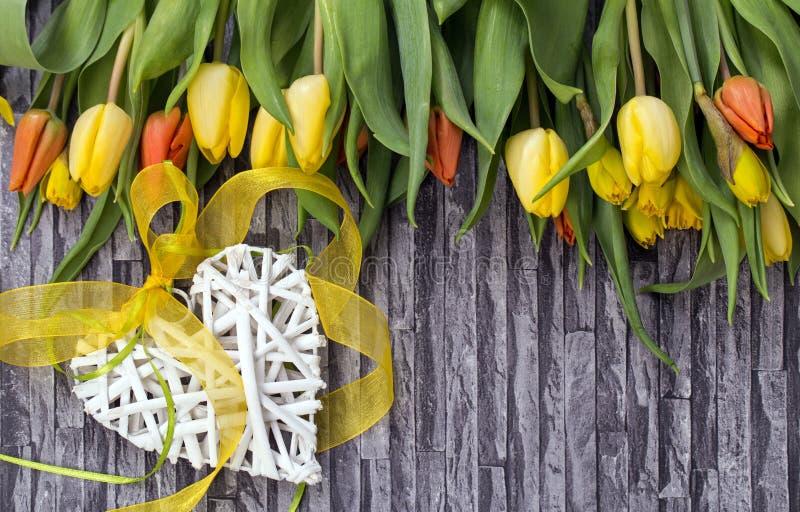 De lente bloeit boeket van gele en rode tulpen en gele narcissen op een grijze achtergrond met het motief van de muur en baksteen stock afbeeldingen