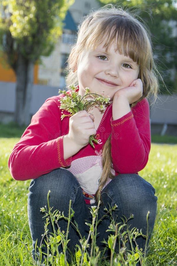 De lente in de zitting van het park mooie meisje op graswi royalty-vrije stock afbeelding