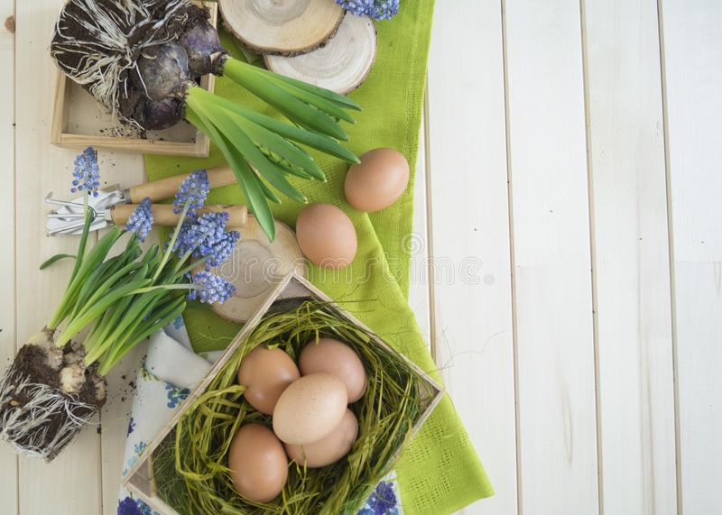 De lente decoratieve samenstelling Bloemen in een mand en potten van hyacint, muscari, narcissen Houten achtergrond stock afbeeldingen