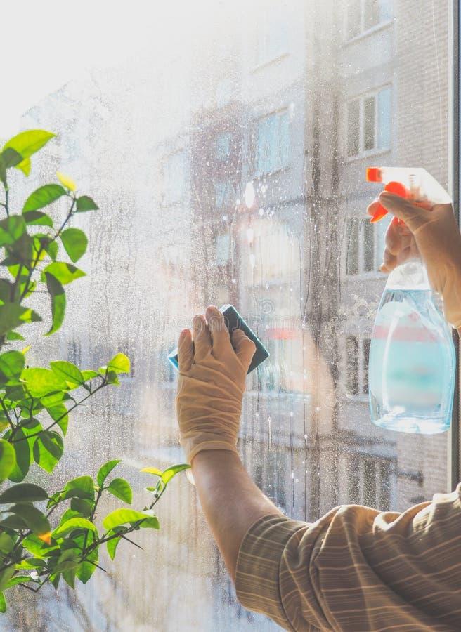 De lente het schoonmaken - schoonmakende vensters De vrouwen` s handen wassen het venster, het schoonmaken royalty-vrije stock afbeelding