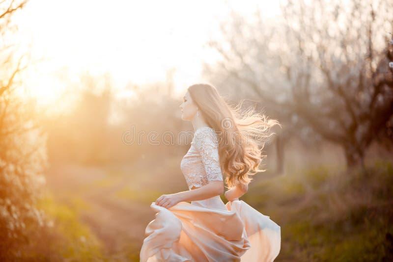 De lente komt Gelukkige mooie jonge vrouw die en pret in bloesempark in werking stellen hebben stock foto's