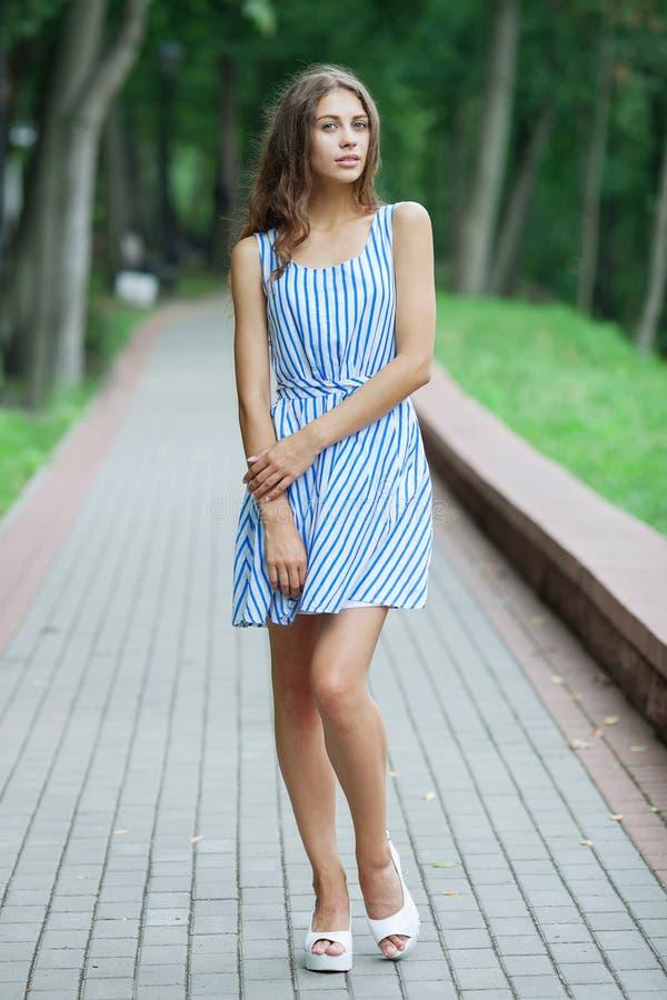 De lente mooie vrouw in de zomerkleding het stellen in groen park die van weekend genieten Speels en mooi Kaukasisch meisje op wa stock foto's
