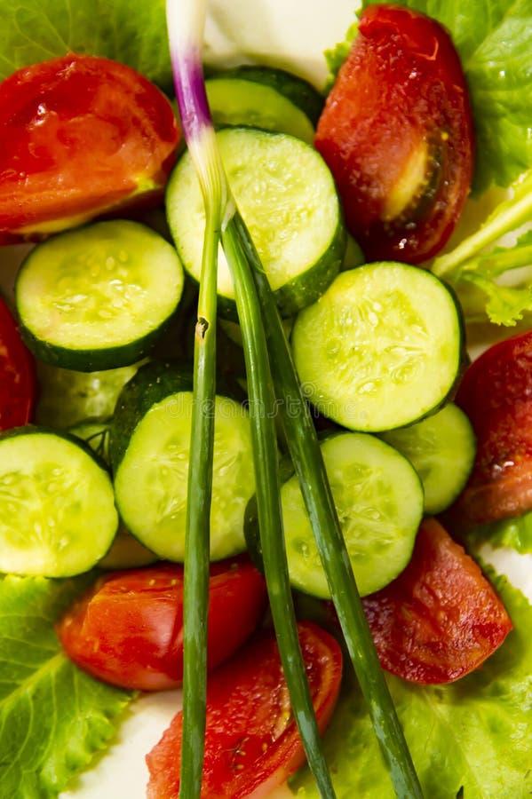 De lente plantaardige salade op een geruit tafelkleed Komkommer, tomaat, groene salade, ui stock fotografie