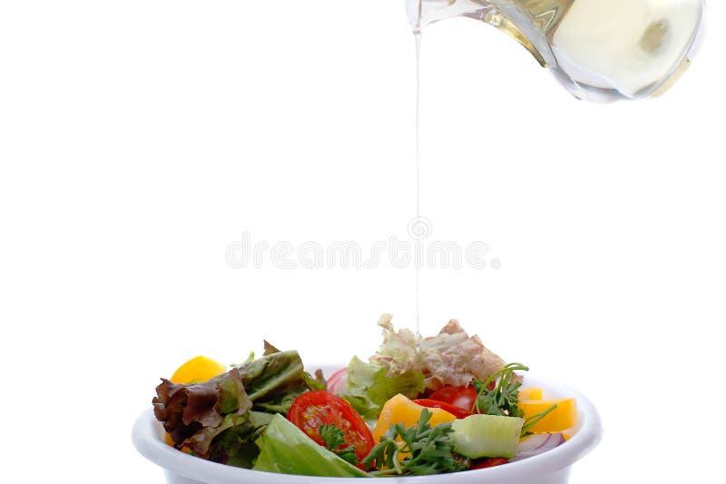 De lente plantaardige salat met de kaas en de olijven van de tomatenui olijfolie het gieten in kom salat stock afbeelding