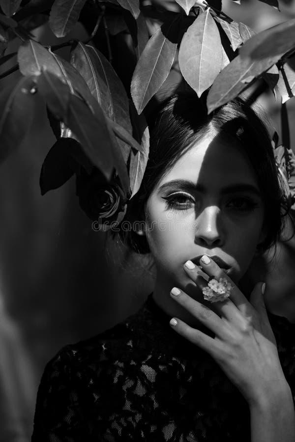 De lente, de zomervakantie vrouw die met modieuze make-up witte bloem in mond houden stock foto