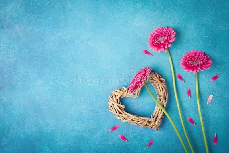 De lenteachtergrond met roze bloemen, hart en bloemblaadjes Groetkaart voor vrouwendag vlak leg stijl Hoogste mening stock foto's