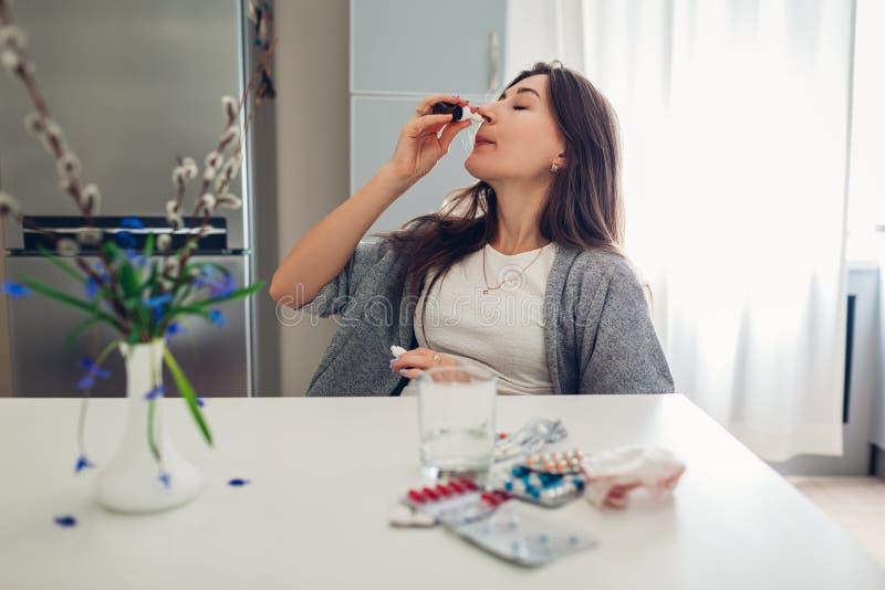 De lenteallergie Vrouw gebruikend neusdalingen tegen seizoengebonden allergie en nemend pillen op keuken Gezondheidszorg en Genee royalty-vrije stock afbeeldingen
