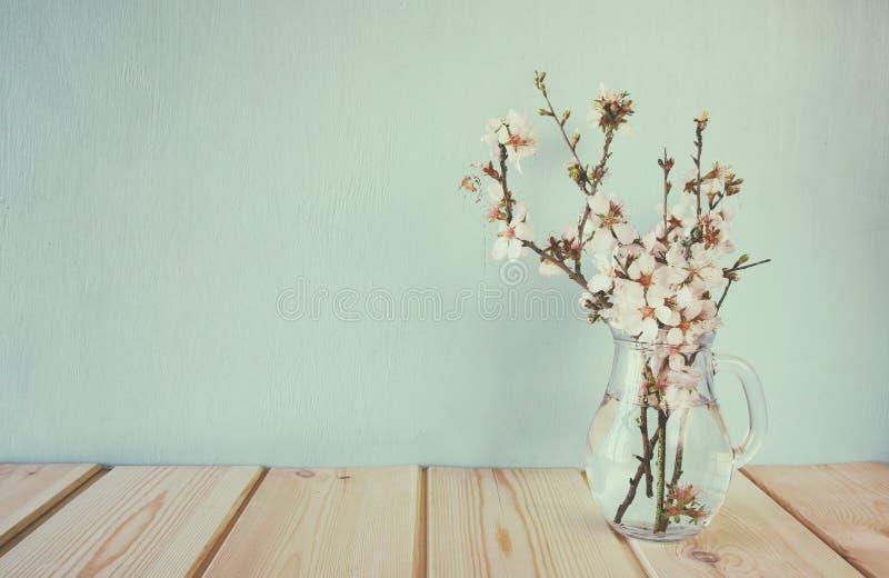 De lenteboeket van bloemen op de houten lijst met muntachtergrond gefiltreerd en gestemde wijnoogst stock foto's