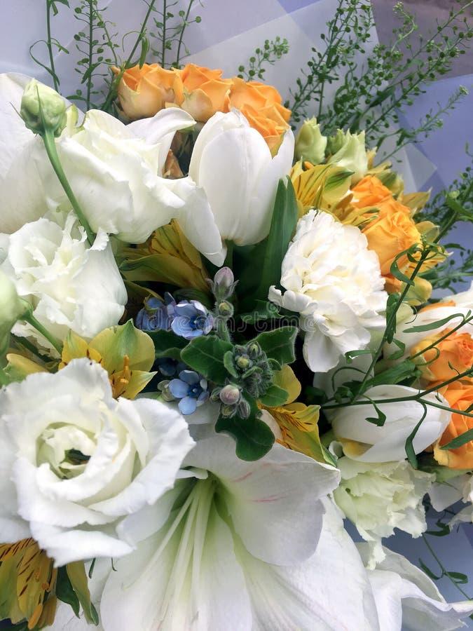 De lenteboeket van gemengde kleurrijke bloemen Bloeit boeket met inbegrip van witte tulpen, witte amarilis, gele rozen blauwe oxy stock afbeelding